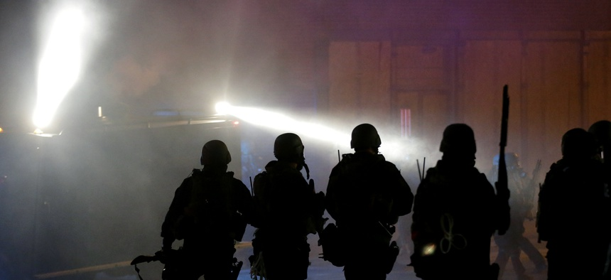 Police advance to disperse the crowd after firing tear gas outsidethe Ferguson city hall, on Tuesday, Nov. 25, 2014, in Ferguson, Mo.