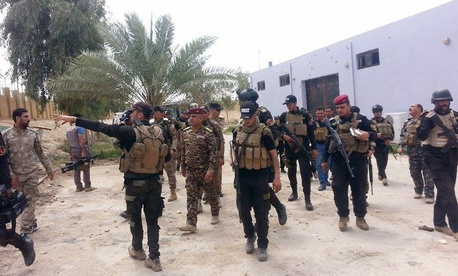 Iraqi security forces and tribal fighters prepare to attack Islamic State group militants on al-Houz bridge on the Euphrates river in Ramadi, on April 24, 2015.