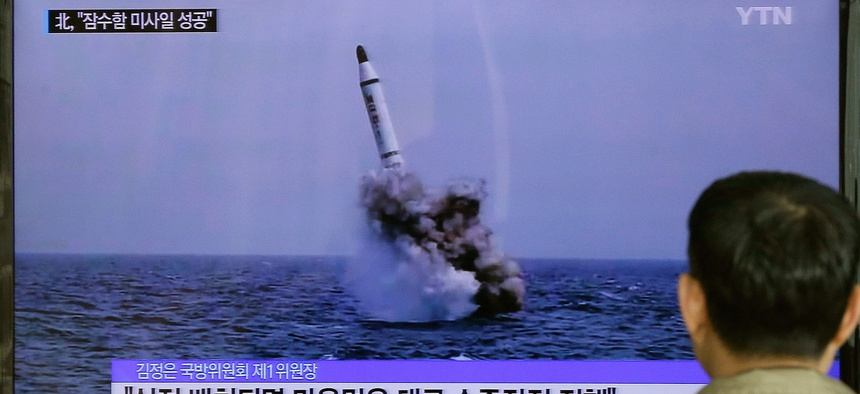 A South Korean man watches a TV news program showing North Korea's ballistic missile believed to have been launched from underwater, Saturday, May 9, 2015.
