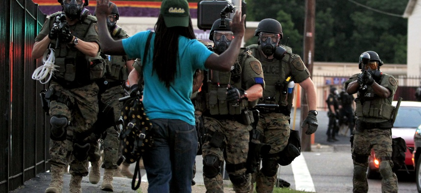 In this Aug. 11, 2014 photo, police wearing riot gear point their weapons before arresting a man in Ferguson, Mo.