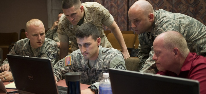 A Navy commander works with teammates at the U.S. Army's Cyber Center of Excellence at Fort Gordon, Georgia.