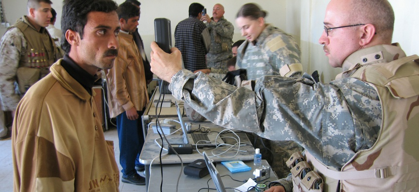 An unidentified U.S. soldier conducts an iris scan on an Iraqi man during an Iraqi army recruiting drive in the city of Ramadi on Monday March 27, 2006.