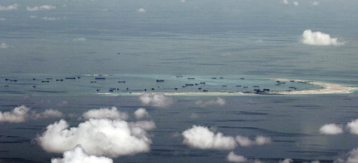 This aerial photo taken through a glass window of a military plane shows China's alleged on-going reclamation of Mischief Reef in the Spratly Islands in the South China Sea Monday, May 11, 2015.