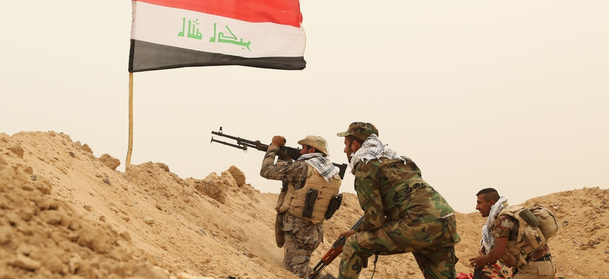 Fighters from the Badr Brigades Shiite militia clash with Islamic State militant group at the front line, on the outskirts of Fallujah, Anbar province, Iraq, Monday, June 1, 2015.