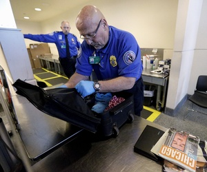 A TSA agent checks a bag at a security checkpoint area at Midway International Airport in Chicago, on November 21, 2014.