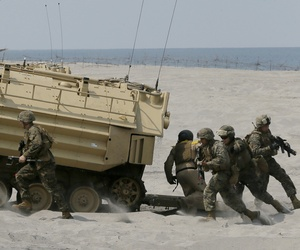U.S. troops disembark from their amphibious assault vehicle during a combined assault exercise at a beach facing one of the contested islands off the South China Sea known as Scarborough Shoal in the West Philippine Sea on Tuesday, April 21, 2015.