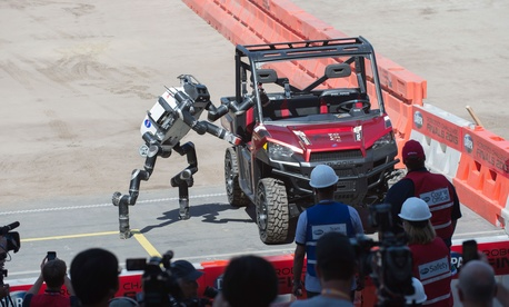 RoboSimian, a simian-inspired robot from the Jet Propulsion Labs, exits a vehicle during the Defense Advanced Research Projects Agency (DARPA) Robotics Challenge (DRC) June 5 in Pomona, Calif.