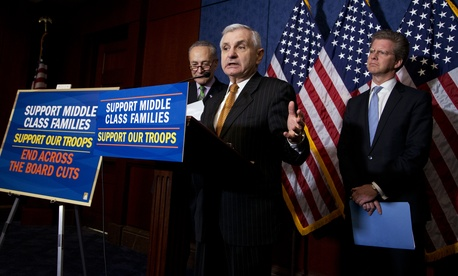 Sen. Jack Reed, D-R.I., center, with Sen. Chuck Schumer, D-N.Y., back left, and Office of Management and Budget Director Shaun Donovan, right, speaks to reporters during a news conference on Capitol Hill, on March 12, 2015.