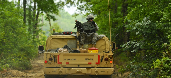 A soldier, assigned to 1221st Route Clearance Company, South Carolina Army National Guard, gunner on top a HMMVV scans for threats during route clearance operations at McCrady Training Center, Eastover, S.C., June 24, 2014.
