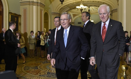 Senate Majority Leader Mitch McConnell of Ky., second from left, walks to the podium to speak to reporters following the weekly Republican luncheon on Capitol Hill in Washington, Tuesday, June 16, 2015.