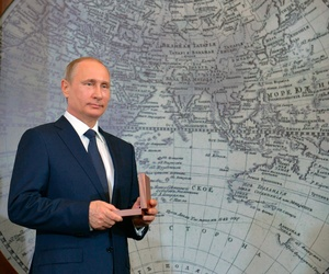 Russian President Vladimir Putin holds an award during a meeting of Russian Geographical Society in St Petersburg, Russia, Monday, April 27, 2015.
