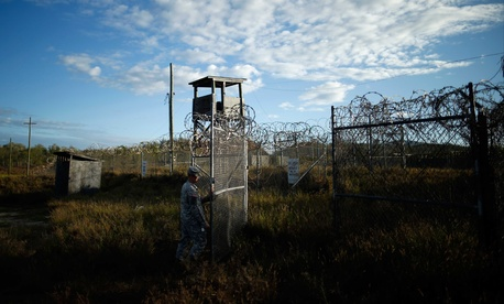 A U.S. soldier closes the gate at a now-abandoned detention facility at Naval Station Guantanamo Bay, Cuba, Nov. 13, 2013.