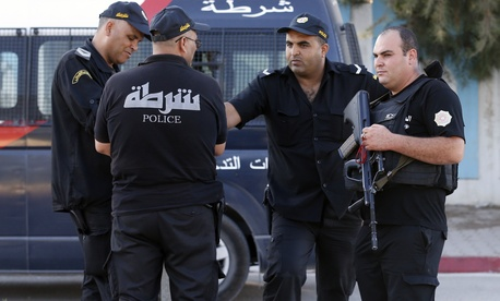 Tunisian police officers guard the street near the attacked Imperial Marhaba hotel in Sousse, Tunisia, Saturday, June 27, 2015.