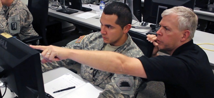 A California National Guard soldier assists another analyst during a simulated virus attack at 2014 Cyber Shield exercise.