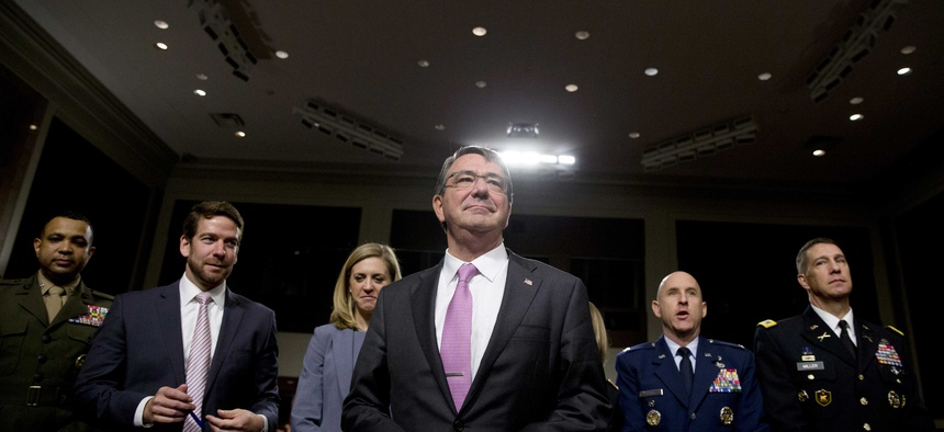 Defense Secretary Ash Carter stands by his seat as he arrives at the Senate Armed Services Committee hearing on Capitol Hill in Washington, Tuesday, July 7, 2015.