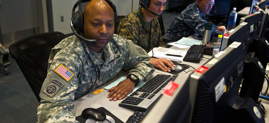 Two cyber operators look at their workstations during Exercise Red Flag, on March 12, 2014.