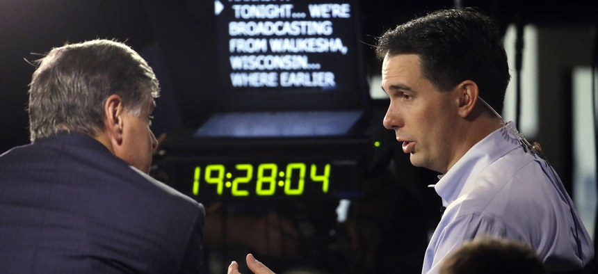 Wisconsin Gov. Scott Walker, right, gives a broadcast interview after announcing that he is running for the 2016 Republican presidential nomination at the Waukesha County Expo Center, Monday, July 13, 2015, in Waukesha, Wis.