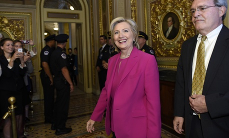 Hillary Clinton walks with David McCallum, deputy chief of staff for Sen. Harry Reid, as they arrive for the weekly policy luncheon with Senate Democrats on Capitol Hill, on July 14, 2015.