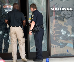 Police officers enter the Armed Forces Career Center through a bullet-riddled door after the shooting Thursday.