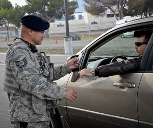 A California Air National Guard NCO checks an idenitification card at the main gate to Moffett Federal Airfield, Calif., on Dec. 8, 2014.