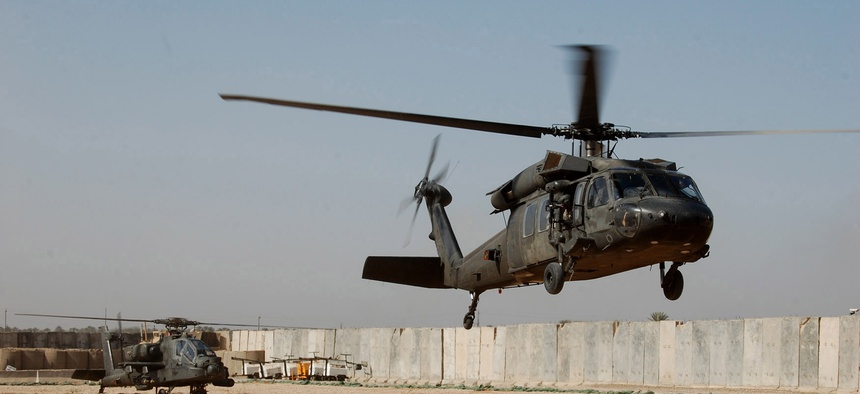 A Blackhawk and Apache helicopter from the 3rd and 4th Battalions prepare to depart Camp Dolby during an operation six miles south of Baghdad.