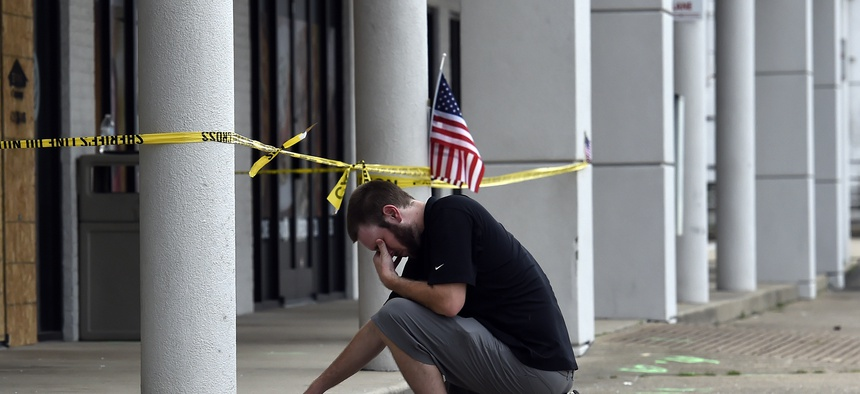 Ryan Scafe prays in front of the Armed Forces Career Center Monday, July 20, 2015, in Chattanooga, Tenn.