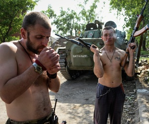 A Russia-backed rebel smokes, holding rifles in his both hands, on the outskirts of Donetsk, eastern Ukraine, Tuesday, May 26, 2015.
