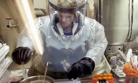 A microbiologist at Life Sciences Test Facility at Dugway Proving Ground, Utah, works in a specialized airtight enclosure designed for use with deadly agents.
