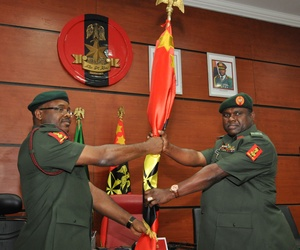 In this Monday, Jan. 20, 2014 file photo, Former chief of Army staff, Lt. Gen. Azubuike Ihejirika, left, holds a flag with Maj. Gen. Kenneth Tobiah Jacob Minimah, the newly appointed chief of army staff, during the handover ceremony in Abuja, Nigeria.