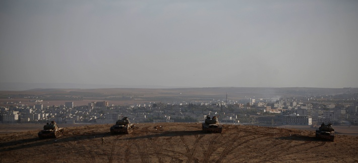 Turkish soldiers hold their positions with their tanks on a hilltop in the outskirts of Suruc, at the Turkey-Syria border, Oct. 10, 2014.