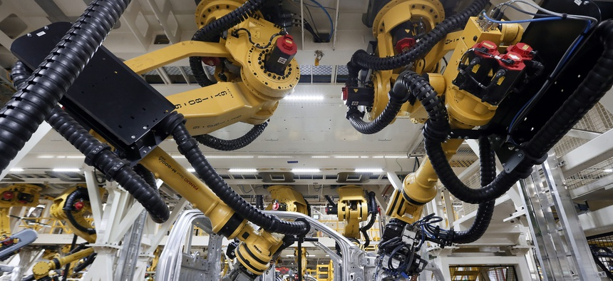 n this Nov. 11, 2014 file photo, robots install rivets on a 2015 Ford F-150 truck at the Dearborn Truck Plant in Dearborn, Mich.