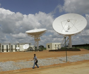 In this Oct. 28, 2008 file photo, a man walks past a satellite dish station in El Sombrero, Venezuela.