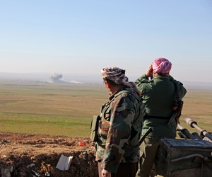 In this Tuesday, Jan. 20, 2015 image released by the Kurdistan Region Security Council (KRSC), Kurdish peshmerga forces watch smoke rise as fighters target Islamic State group positions in northern Iraq.