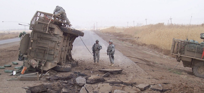 A Stryker fighting vehicle lies on its side after surviving a buried IED blast in Iraq in 2007.