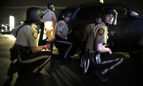 Police take cover behind a vehicle during a protest in Ferguson, Mo., Sunday, Aug. 9, 2015.