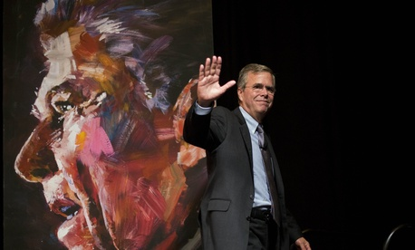Republican presidential candidate Jeb Bush waves to the crowd while walking past a portrait of former President Ronald Reagan after speaking at the RedState Gathering Saturday, Aug. 8, 2015, in Atlanta.