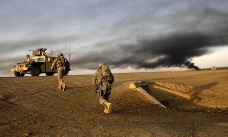 U.S. Army Sgts. Sean Bundy and Dennis First search for IEDs near Al Muradia village, Iraq, in 2007. The smoke is from a controlled IED detonation.