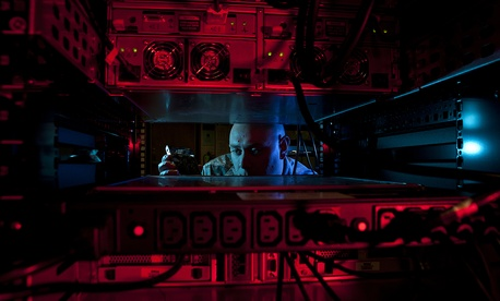 A U.S. Airman inserts a hard drive into the network control center retina server at Altus Air Force Base, Okla., Jan. 24, 2014.