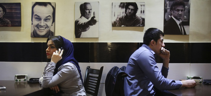 Young Iranian adults sit at a cafe, backdropped, with pictures of Western celebrities in Tehran, Iran.