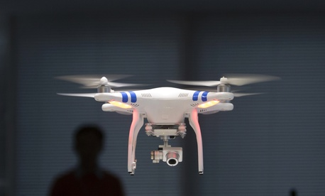 A staff member from DJI Technology Co. demonstrates remote flying with his Phantom 2 Vision+.