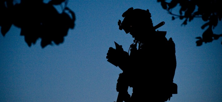 A U.S. Navy SEAL team member, with Special Operations Task Force – South, reviews a map of the objective area during the early morning hours of a village clearing operation in Shah Wali Kot District, June 25, 2011, Kandahar province, Afghanistan.