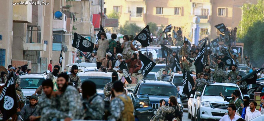 Photo from the Raqqa Media Center of the Islamic State group, a Syrian opposition group, fighters from the Islamic State group parade in Raqqa, north Syria.