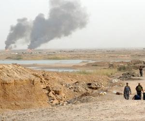 In this Thursday, Aug. 6, 2015 photo, smoke rises as Iraqi security forces backed by Shiite and Sunni pro-government fighters bomb Islamic State group positions at the front line in the eastern suburbs of Ramadi, Anbar province, Iraq.