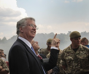 British Secretary of State for Defense, Michael Fallon, watches proceedings as British serviceman teach Ukrainian soldiers on the military base outside Zhitomir, Ukraine, Tuesday, Aug. 11, 2015.