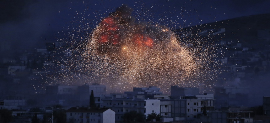 Thick smoke and flames from an airstrike by the U.S.-led coalition rise in Kobani, Syria, as seen from a hilltop on the outskirts of Suruc, at the Turkey-Syria border, Monday, Oct. 20, 2014.