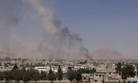 This image made from video posted online by the Shaam News Network, a loosely organized group opposed to Bashar Assad, on Sunday, Aug. 16, 2015, which has been verified and is consistent with other AP reporting, shows smoke rising over a Damascus suburb.