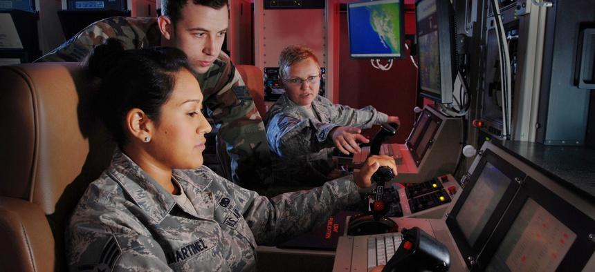 USAF Master Sgt. Jennifer Oberg explains the features of a ground control station to Staff Sgt. Jason Avera and Senior Airman Raquel Martinez.