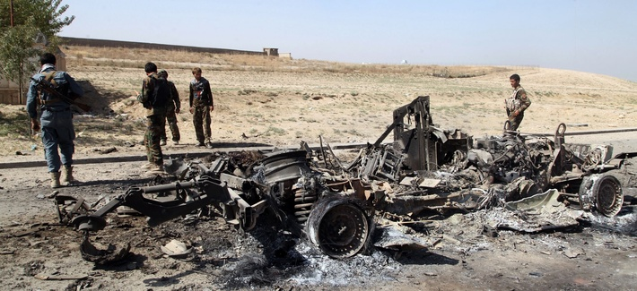 Afghan security personnel walk around a burnt out vehicle near Kunduz city, north of Kabul, Afghanistan, Thursday, Oct. 1, 2015.