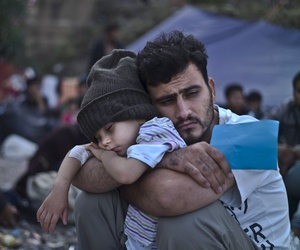 A Syrian refugee child sleeps on his father's arms while waiting at a resting point to board a bus, after arriving on a dinghy from the Turkish coast to the northeastern Greek island of Lesbos, Sunday, Oct. 4 , 2015.
