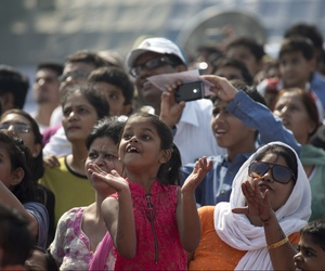 On the day India's air force chief announced women would be allowed to become fighter pilots, a girl looks skyward to watch the military air show at Air Force Day at Hindon Air Force base near New Delhi, India, Oct. 8, 2015.